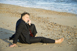 anxious looking businessman using cellphone on the beach poster