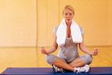 Frau meditiert in Turnhalle