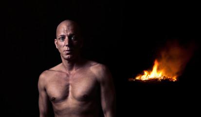 Mann vor der Feuerstelle