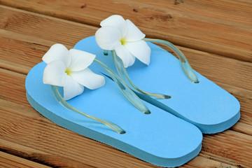 sandales bleues fleuries sur planches terrasse de sauna