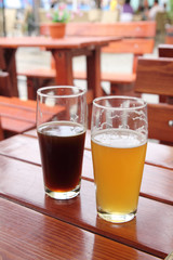 Two glasses of beer on wooden desk