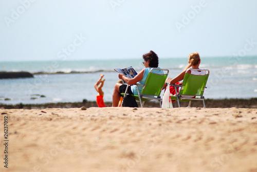 Familia en la playa sentadas en las hamacas de - Hamacas de playa ...
