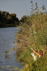 girl fisherman on the riverside, and dog