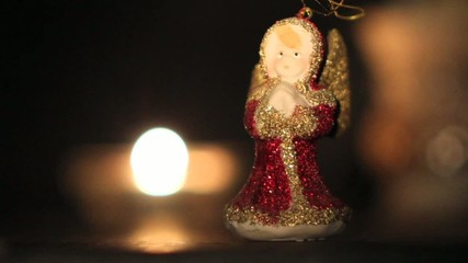Christmas angel with dancing lights of candle