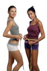 Two women measure waist belly by metre-stick