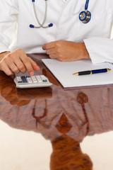 Arzt mit Taschenrechner. Kostenrechnung Arztpraxis