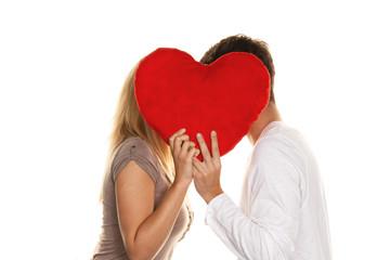 Verliebtes Paar küßt sich hinter einem Herz. Liebe ist schö