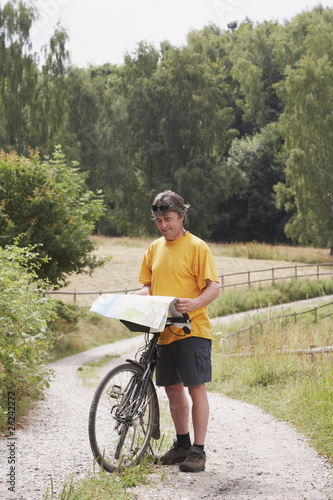 man with bicycle stopping on rural road and looking at map