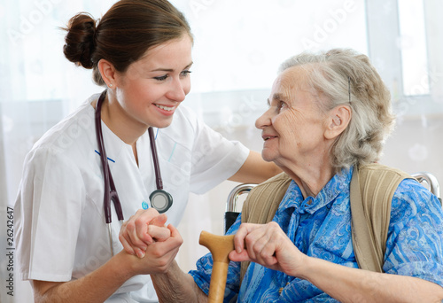 Senior woman is visited by her doctor or caregiver