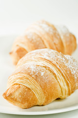 fresh croissants on white plate with powdered sugar
