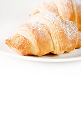 fresh croissants on white plate with empty space below