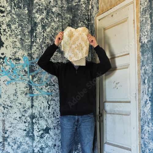Figure obscured by torn wallpaper in abandoned house.