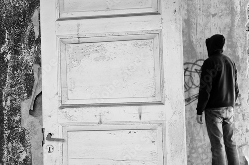 Hooded figure in abandoned house. Black and white.