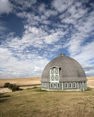 Round barn against a blue sky.