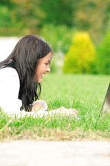 Student lying down on the grass working on laptop