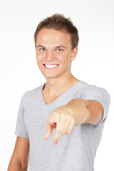 Portrait of a young man pointing at you, isolated on white