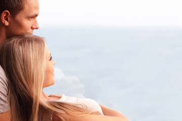 Young loving couple looking at a beautiful seaview in the window
