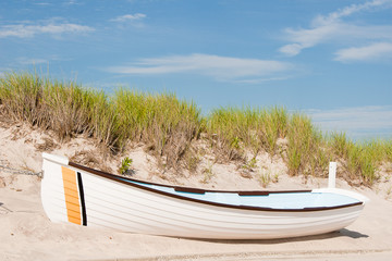 White Lifeguard Boat on the Sand In Front of a Sand Dune