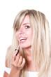 happy beautiful woman applying lipstick isolated on white