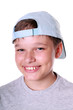 Isolated portrait of a young boy in cap smiling