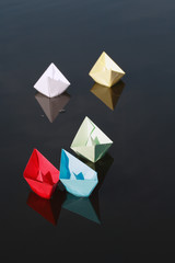 Set of motley paper boats on water background