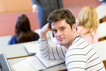 Handsome male student looking at the camera during an university