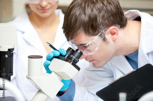 Caucasian male scientist holding pen and clipboard looking throu
