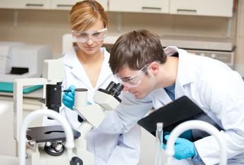 Two scientists observing something with a microscope