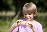 A young boy eating a sandwich