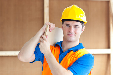 Confident young male worker with a yellow helmet carrying a wood