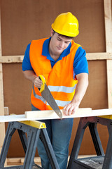 Handsome male worker wearing a yellow hardhat sawing a wooden bo