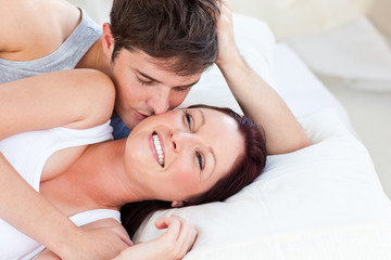 Caring caucasian couple lying on bed in the bedroom