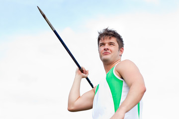 Handsome male throwing a javelin outdoors