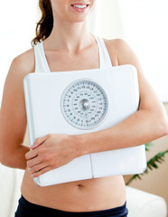 Close-up of a fit hispanic woman holding a scale in her living-r