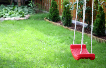 An empty swing on green grass background