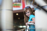 Young beautiful woman near a handrail poster