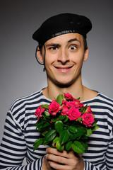 Funny emotional romantic sailor man holding rose flowers prepare