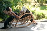 Fototapety Donna legge su sedia a dondolo