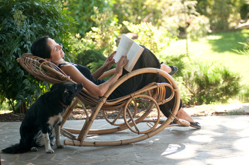 Donna legge su sedia a dondolo