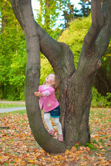 Girl (3 years) leaned to tree. Looking up with surprise