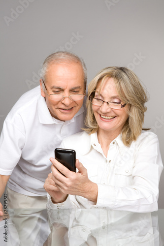 Happy senior people with a phone