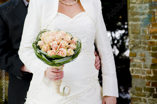 Bride and groom showing wedding bouquet
