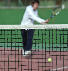 Tennis player in action (selective focus, focus on the net).