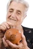 Elderly woman depositing money in piggy bank isolated over white poster