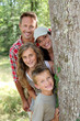 Smiling family standing behind a tree