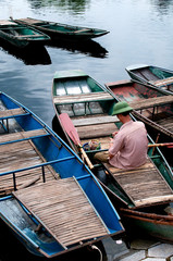 Boatman on a row wooden boat