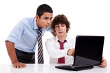 Two young businessmen working together on a laptop