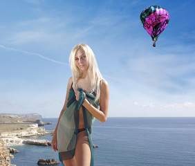 Blonde in a green pareo  on beach with baloon in sky