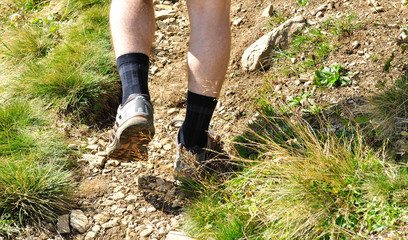 Man runs along a mountain path, closeup feet, sneakers