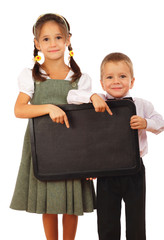 Littles schoolgirl and boy with empty chalkboard